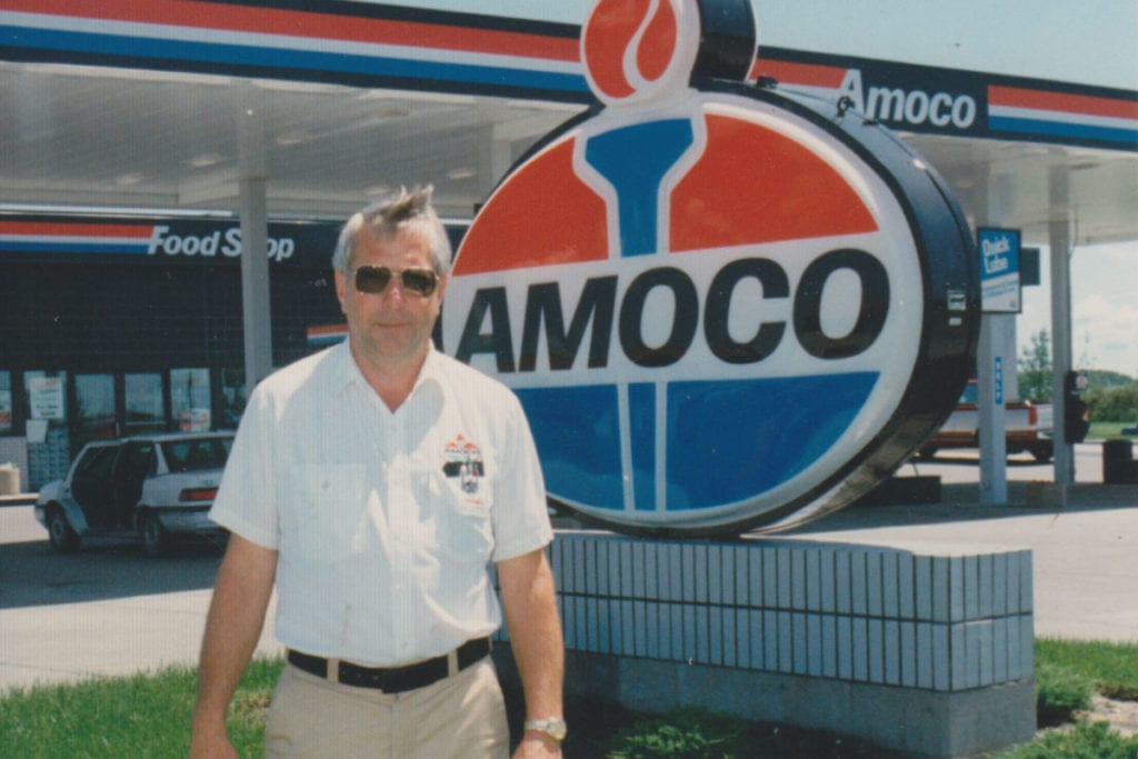 Loren Dusterhoft stands in front of Amoco sign